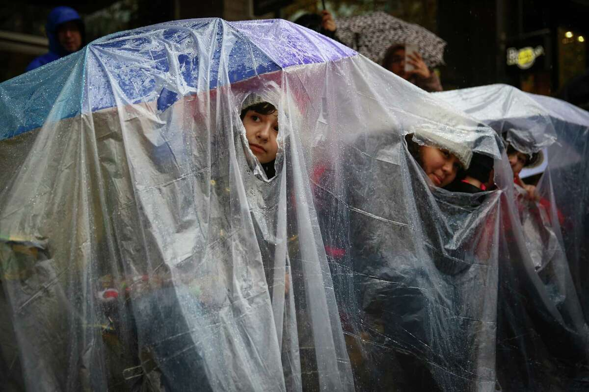 Katie Johnston, 17, keeps dry while watching the Macy's Holiday Parade with Audrey Remle, 16, and Gracie Johnston, 12, in Seattle on Friday, November 28, 2014. It rained on the parade but that didn't stop thousands of people from coming out the watch the annual event.