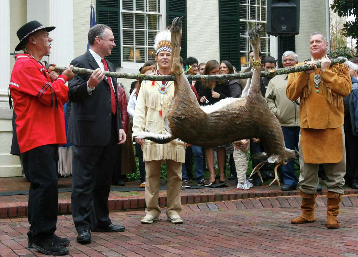 FILE - This Nov. 25, 2009, file photo shows Pamunkey Councilmen Jeff Brown, left, and Gary Miles, hold a deer as their Chief Kevin Brown presents it to Gov. Tim Kaine, second from left, during the annual tax tribute from the Virginia Indians to the Virginia governor in Richmond, Va. Several members of the Congressional Black Caucus are urging the Obama administration to withhold federal recognition of the Pamunkey tribe in southeast Virginia because of its history of banning intermarriage with blacks. (AP Photo/Richmond Times-Dispatch, Alexa Welch Edlund, File)