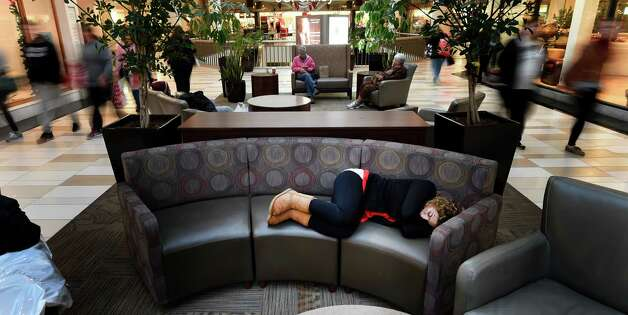 One shopper gave in to exhaustion as others continue their quests on Black Friday morning Nov. 28, 2014 at Crossgates Mall in Albany, N.Y.        (Skip Dickstein/Times Union) Photo: SKIP DICKSTEIN / 00029595A