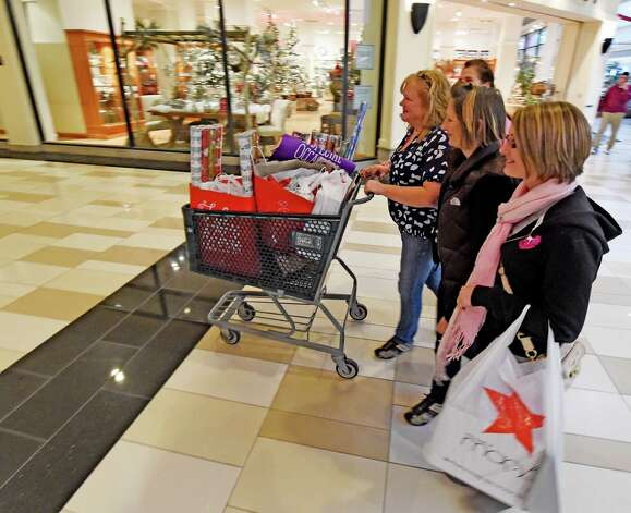 Shoppers Michelle Steadman, left, Diane LaJoy, center and Patty Steadman go to their car with the first cart full of gifts on Black Friday morning Nov. 28, 2014 at Crossgates Mall in Albany, N.Y.        (Skip Dickstein/Times Union) Photo: SKIP DICKSTEIN / 00029595A