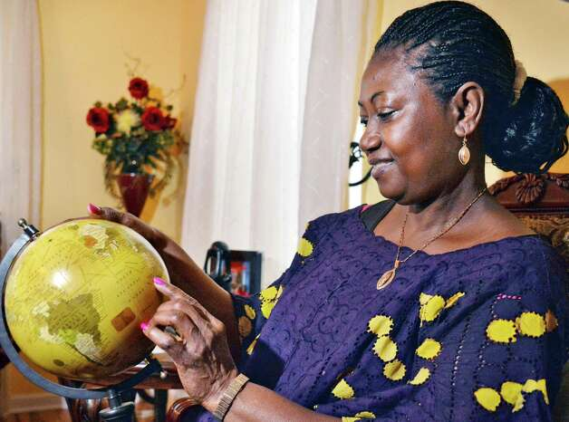 Fatmata Hilton points out the African nation of Sierra Leone on a globe at her home Wednesday Nov. 26, 2014, in Cohoes, NY.  (John Carl D'Annibale / Times Union) Photo: John Carl D'Annibale / 00029611A