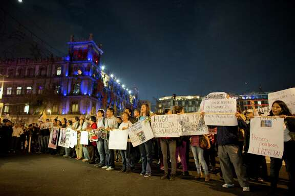 Protestors hold up signs containing slogans and the names of 11 people detained in a demonstration days earlier, as they march to call for the return of 43 missing students and the liberation of the detained, in Mexico City, Tuesday, Nov. 25, 2014. Nearly two months after the students disappeared following an attack by police, protests only continue to multiply, as citizens demand that the government find the missing students alive. (AP Photo/Rebecca Blackwell)