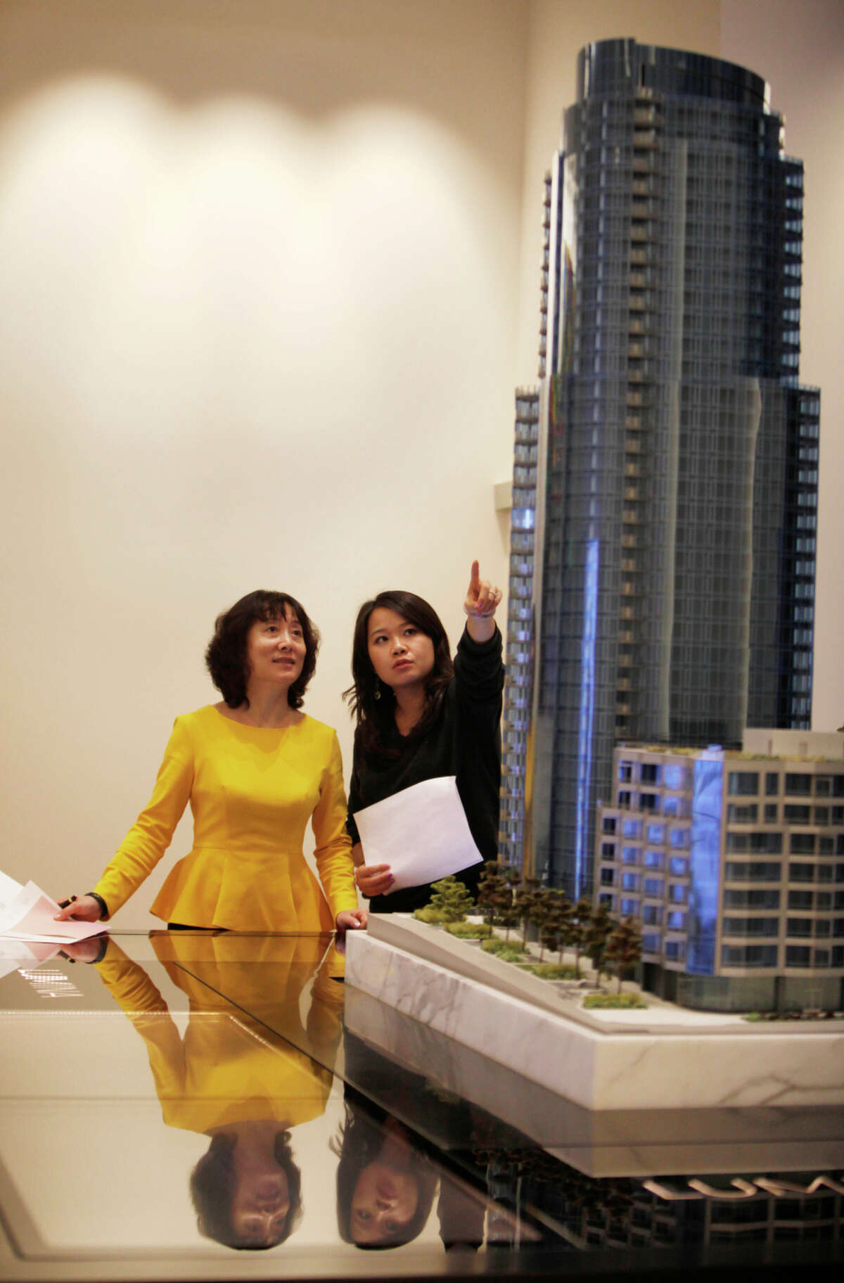 Lumina sales associate Yang Chen (right) talks with Donna Li of Mountain View, who may face foreign buyers with cash.