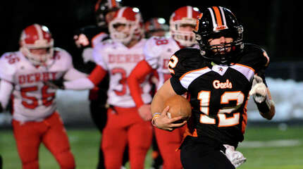 Shelton's Mark Piccirillo carries the ball on his way to a third quarter touchdown, during holiday football action against Derby in Shelton, Conn., on Friday Nov. 28, 2014.