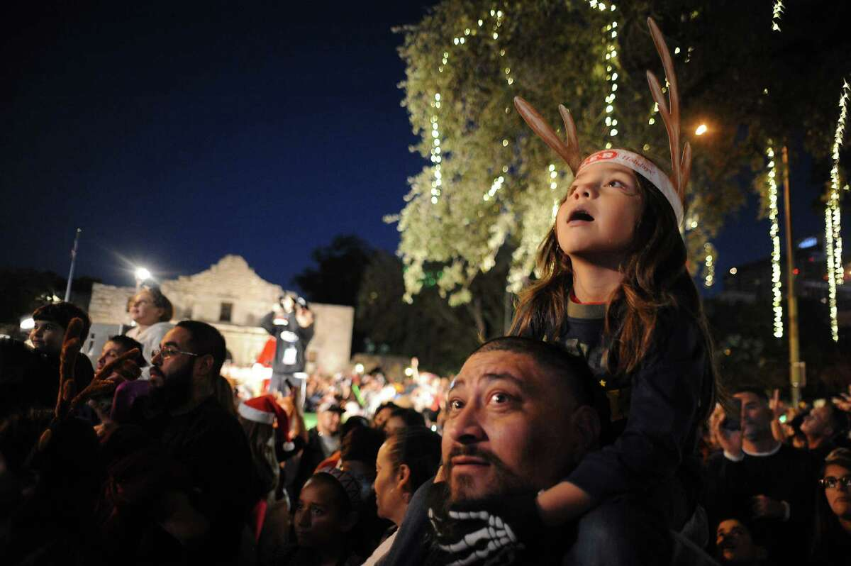 Zackery Dominguez, 5, watches from his father's shoulders as the city's official Christmas tree is lit during the 30th Annual H-E-B Christmas Tree Lighting Celebration in Alamo Plaza on Friday, Nov. 28, 2014.