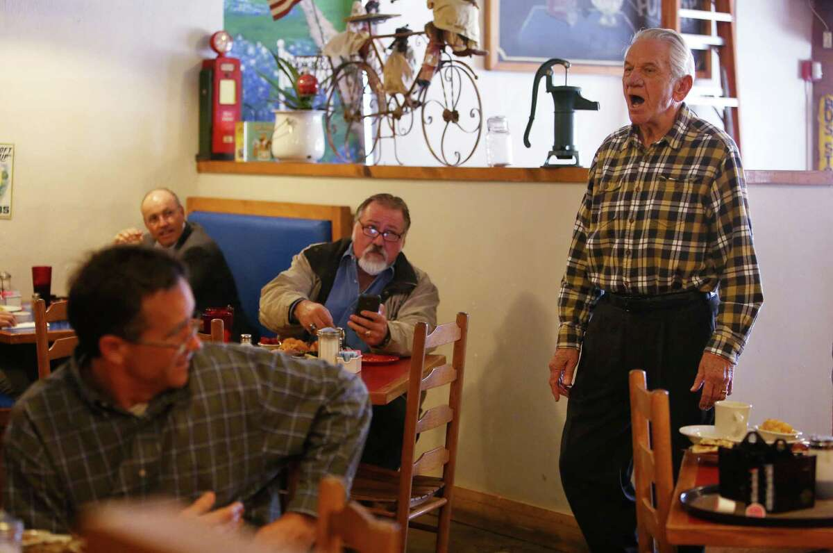 Tom Ott, owner of Humble City Café, sings to patrons during the lunch rush. Residents are trying to preserve the small-town identity of Old Humble amid the development all around it.
