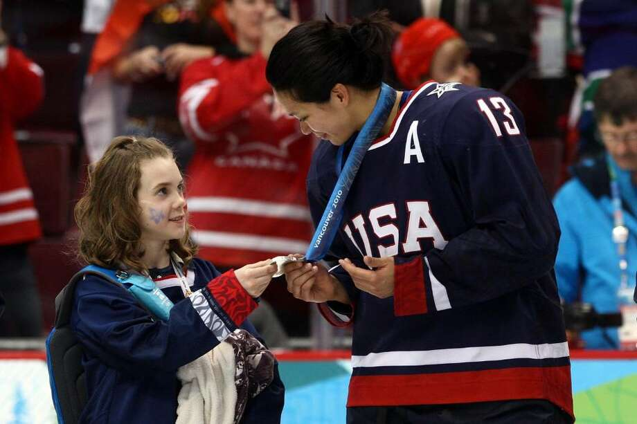 VANCOUVER, BC - FEBRUARY 25:  Julie Chu of the United States shows her silver medal to a youngster following the ice hockey women's gold medal game between Canada and USA on day 14 of the Vancouver 2010 Winter Olympics at Canada Hockey Place on February 25, 2010 in Vancouver, Canada.  (Photo by Bruce Bennett/Getty Images) Photo: Bruce Bennett, Getty Images / 2010 Getty Images
