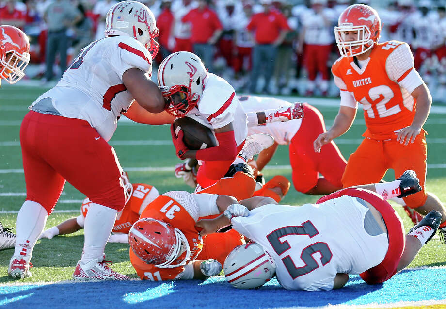 Judson's Demereion Clark (center) scores a touchdown over Laredo United's Danny Cardona during second half action of their Class 6A Division I third-round playoff game Friday Nov. 28, 2014 at Texas A&M Kingsville's Javelina Stadium in Kingsville, Tx. Judson won 55-20. Photo: Edward A. Ornelas, By Edward A. Ornelas, Express-News / © 2014 San Antonio Express-News
