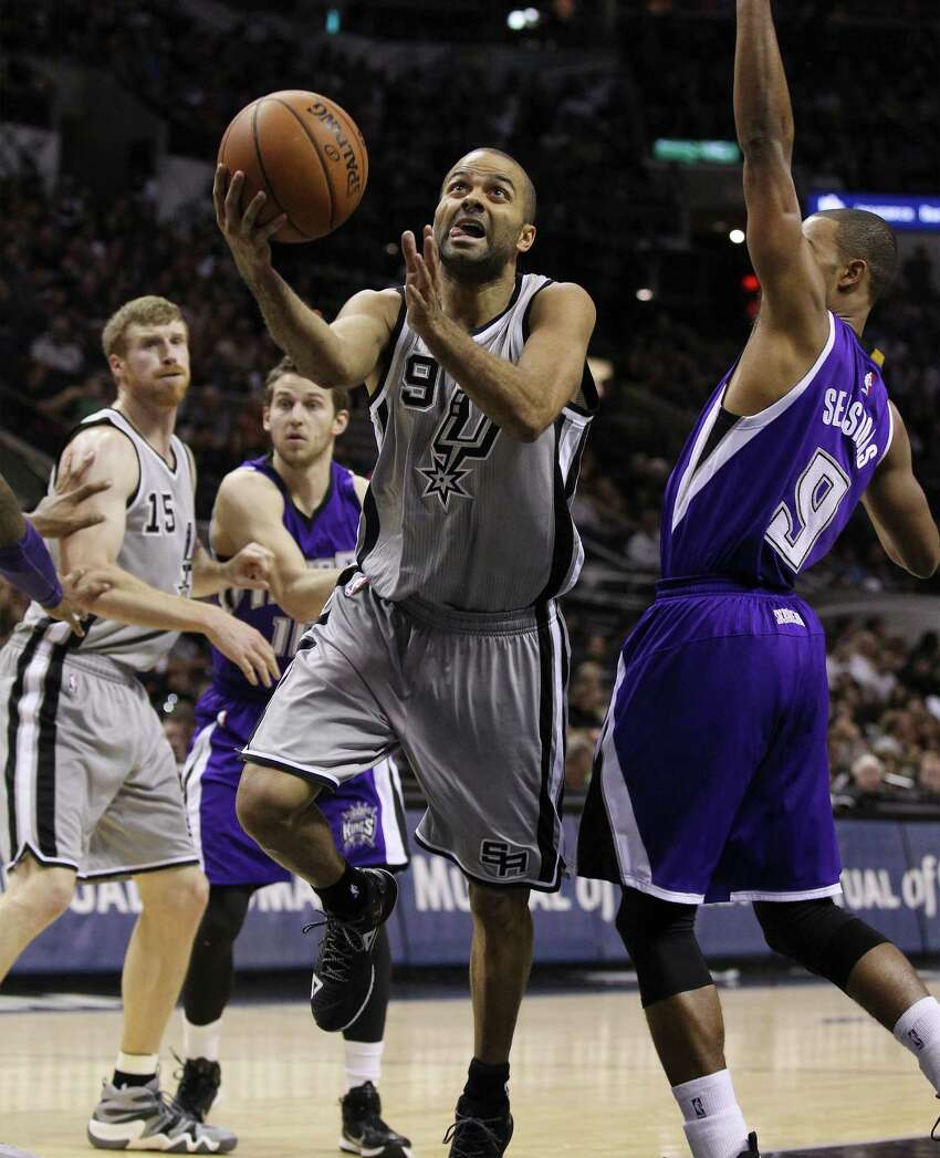 Spurs' Tony Parker (09) speeds past Sacramento Kings' Ramon Sessions (09) at the AT&T Center on Friday, Nov. 28, 2014. (Kin Man Hui/San Antonio Express-News)