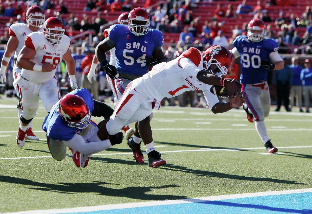 SMU linebacker Jonathan Yenga, left, is unable to stop Houston quarterback Greg Ward Jr. (1) from diving into the end zone for a touchdown during the second half of an NCAA college football game Friday, Nov. 28, 2014, in Dallas. (AP Photo/The Dallas Morning News, Brandon Wade) MANDATORY CREDIT; MAGAZINES OUT; TV OUT; INTERNET USE BY AP MEMBERS ONLY; NO SALES