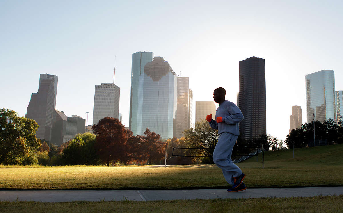 A man jogs through Eleanor Tinsley Park as the sun rises, Friday, Nov. 28, 2014, in Houston.