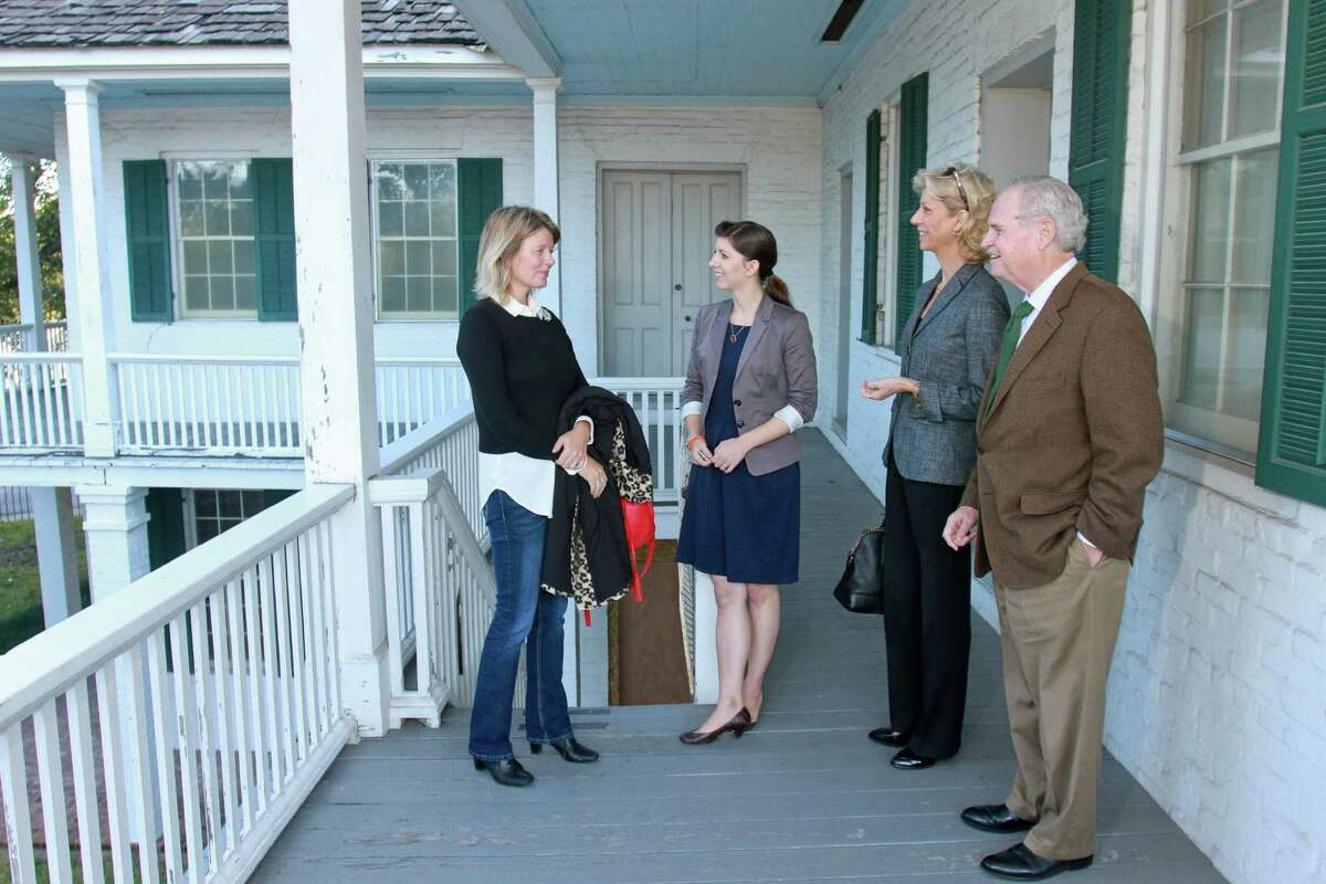 Margaret Justus, from left, Emily Ardoin, Margaret Lawler and Jim Furr on the second floor gallery at the top of the exterior staircase of the Kellum-Noble house in Sam Houston Park.