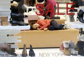 A young girl lies on a couch as the woman she was accompanying checks out shoes while shopping on Black Friday at the Garden State Plaza mall Friday, Nov. 28, 2014, in Paramus, N.J. (AP Photo/Julio Cortez)