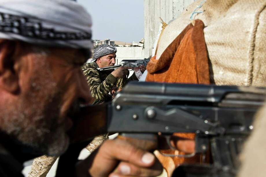 Fighters from the Free Syrian Army (left) and the Kurdish People's Protection Units (center) join forces to fight Islamic State group militants in Kobani, Syria. Photo: Jake Simkin / Associated Press / AP