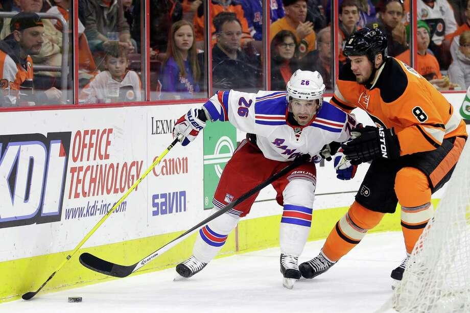 New York Rangers' Martin St. Louis, left, battles with Philadelphia Flyers' Nicklas Grossmann, of Sweden,  for control of the puck during the first period of an NHL hockey game, Friday, Nov. 28, 2014, in Philadelphia. New York won 3-0. (AP Photo/Matt Slocum) Photo: Matt Slocum / Associated Press / AP