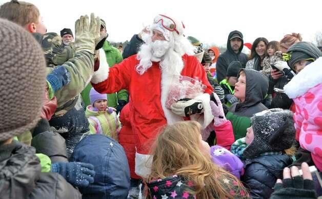 Santa Claus greets children after parachuting onto the EllmsO Christmas Tree Farm Saturday Nov. 29, 2014.  (John Carl D'Annibale / Times Union) Photo: John Carl D'Annibale / 00029634A