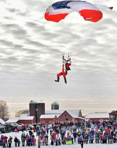 Santa Claus parachutes onto the Ellmsa€™ Christmas Tree Farm as a 1000 eager onlookers cheer Saturday Nov. 29, 2014.  (John Carl D'Annibale / Times Union) Photo: John Carl D'Annibale / 00029634A
