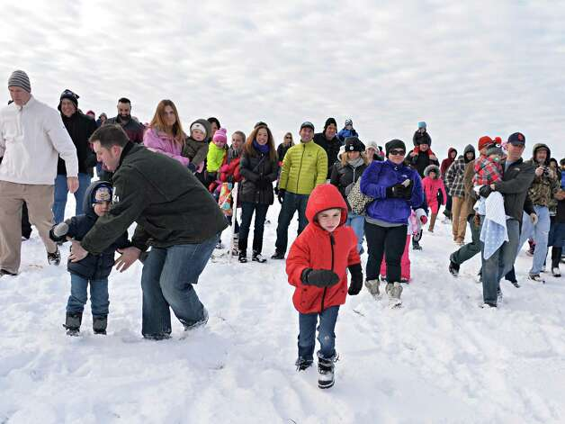 About a 1000 eager onlookers rush toward Santa Claus after he parachuted onto the EllmsO Christmas Tree Farm Saturday Nov. 29, 2014.  (John Carl D'Annibale / Times Union) Photo: John Carl D'Annibale / 00029634A