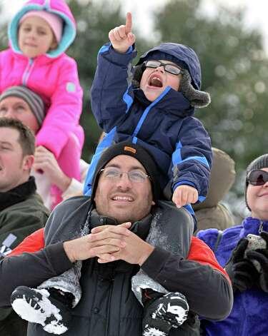 Held high on his father Matt Zichelli's shoulders, 5-year-old Nicholas Zichelli of Ballston catches sight of Santa Claus as he parachutes onto the EllmsO Christmas Tree Farm Saturday Nov. 29, 2014.  (John Carl D'Annibale / Times Union) Photo: John Carl D'Annibale / 00029634A