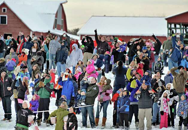About a 1000 eager onlookers watch as Santa Claus parachutes onto the EllmsO Christmas Tree Farm Saturday Nov. 29, 2014.  (John Carl D'Annibale / Times Union) Photo: John Carl D'Annibale / 00029634A