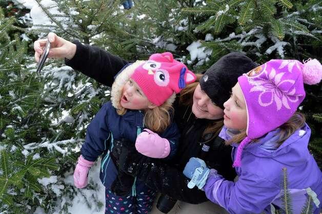 Sarah Csiza and children Quinn, 3, and Allison, 6, of Albany take a selfie in a Christmas tree maze before Santa Claus parachutes onto the EllmsO Christmas Tree Farm Saturday Nov. 29, 2014.  (John Carl D'Annibale / Times Union) Photo: John Carl D'Annibale / 00029634A