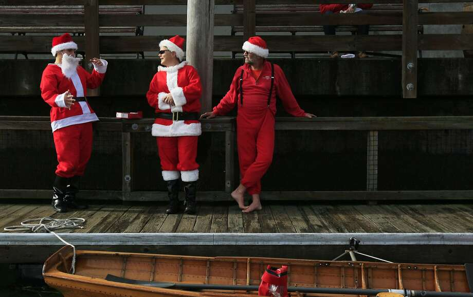 "South End Rowing Club members (from left) Tony Gilbert, Sue Free and Tom Wurm stand on the East Pier 39 marina dock dressed as Santa Claus after rowing boats filled with donated toys to Pier 39 in San Francisco, Calif. Saturday, November 29, 2014 as part of the club's ""Ho Ho Ho Row"" Photo: Jessica Christian, The Chronicle"