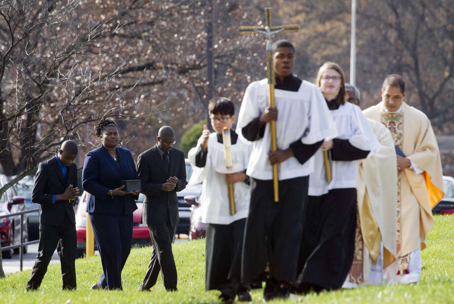 Isatu Salia (second from left), carries her husband's cremated remains in Landover Hills, Md. Photo: Cliff Owen / Associated Press / FR170079 AP