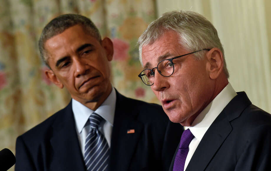 President Obama (left) watches Chuck Hagel as the defense secretary discusses his resignation Monday. Photo: Susan Walsh / Associated Press / AP