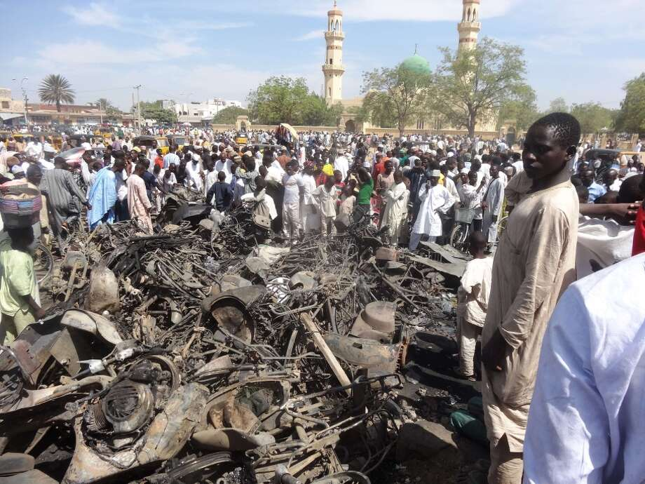 Residents look at motorcycles burnt in the deadly blasts outside the central mosque in northern Nigerian city of Kano. Photo: AMINU ABUBAKAR / AFP/Getty Images / AFP