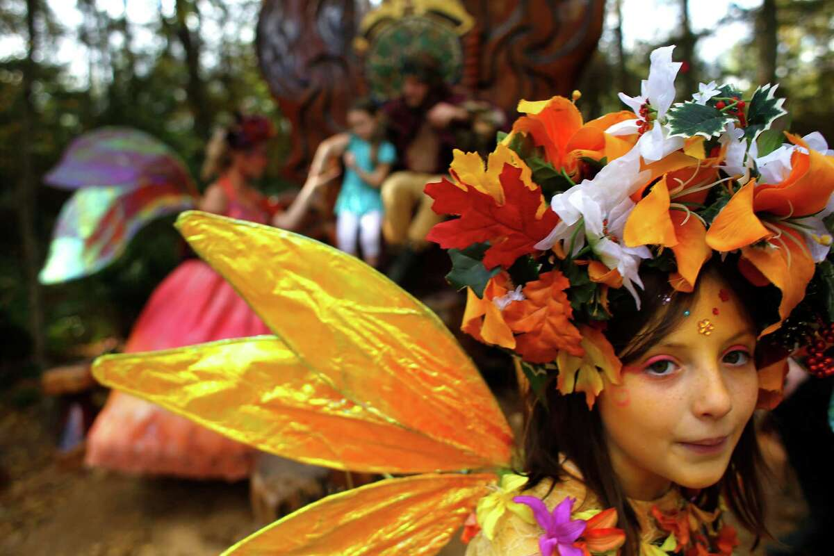 Sophie Deagun plays Flutter Fly the fairy next to Queen Titania and King Oberon, King of the Fairies at the Texas Renaissance Festival Saturday, Nov. 29, 2014, in Todd Mission. Sunday is the last day for the festival this year.