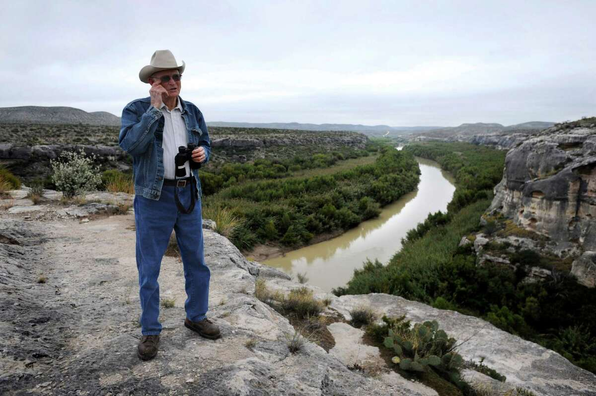 Jackie Skiles, 83, has written a book about Langtry, Texas. He stands on a cliff overlooking the Rio Grande. Mexico is to the left.