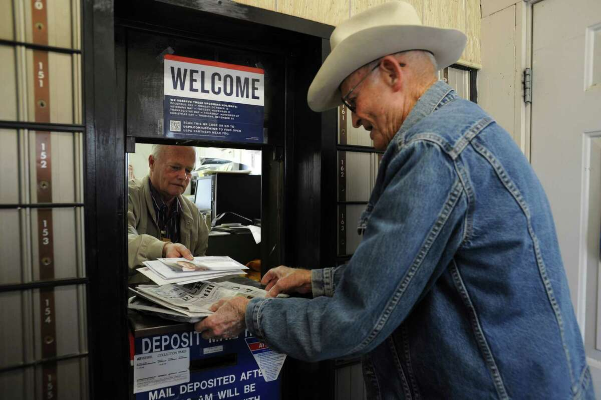 Jackie Skiles, 83, picks up his mail from postmaster Neal Wellman in Langtry, Texas, on Friday, Nov. 21, 2014. Skiles is one of the very residents still living in Langtry.