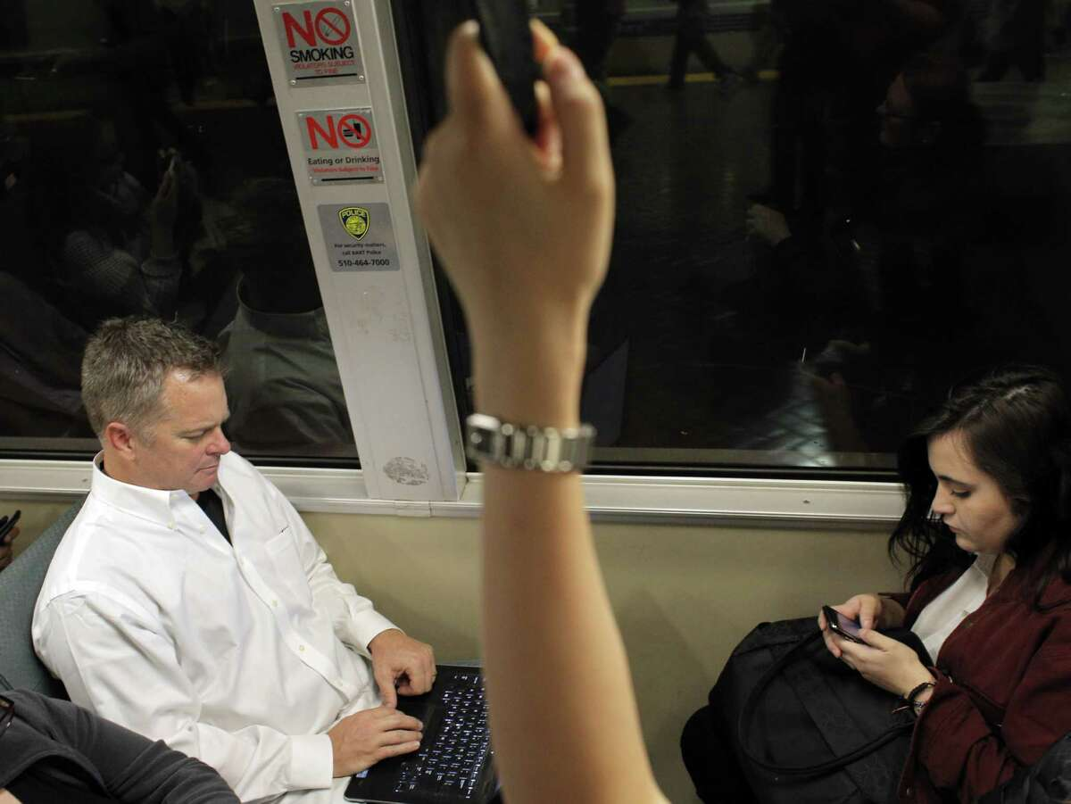 Jeff Knepp, left, settles into a seat across from Antoinette Valerio, right, after boarding an east-bound BART train at Civic Center Station in San Francisco, Calif., to his home in Discovery Bay at rush hour on Monday, November 17, 2014. Knepp rides BART to Dublin (over an hour) then drives (over an hour) to Discovery Bay, so he