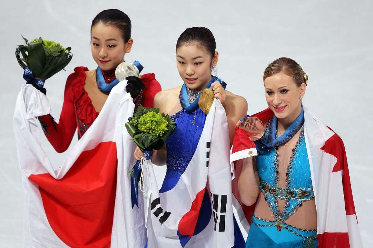 VANCOUVER, BC - FEBRUARY 25: (L-R) Mao Asada of Japan celebrates the silver medal, Kim Yu-Na of South Korea the gold medal and Joannie Rochette of Canada the bronze medal during the medal ceremony for the Ladies Free Skating on day 14 of the 2010 Vancouver Winter Olympics at Pacific Coliseum on February 25, 2010 in Vancouver, Canada. (Photo by Matthew Stockman/Getty Images) *** Local Caption *** Mao Asada;Kim Yu-Na;Joannie Rochette