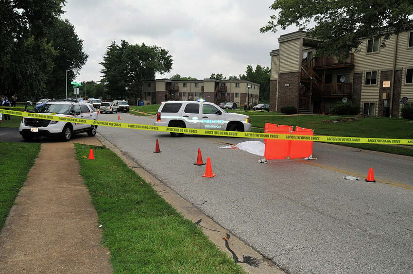 The body of Michael Brown lies on the ground (L) as officials investigate the scene on Canfield Drive on August 9, 2014 in Ferguson, Missouri. Police officer Darren Wilson shot 18-year-old Michael Brown on August 9th, 2014. A St. Louis County 12 member grand jury who reviewed evidence related to the shooting decided not to indict Wilson on charges, sparking large ongoing protests.