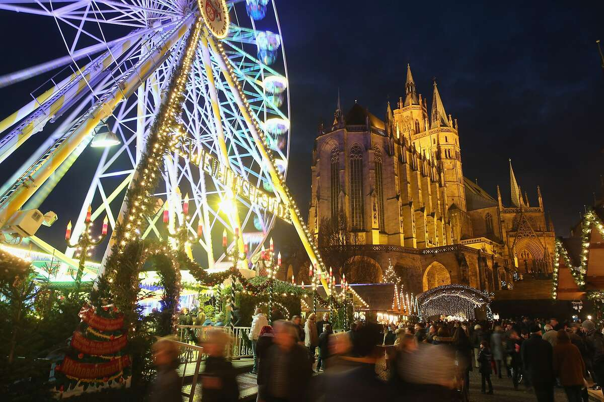 Visitors walk past an illuminated ferris wheel at the annual Christmas market as the Dom cathedral stands behind on Domplatz square in Erfurt, Germany.