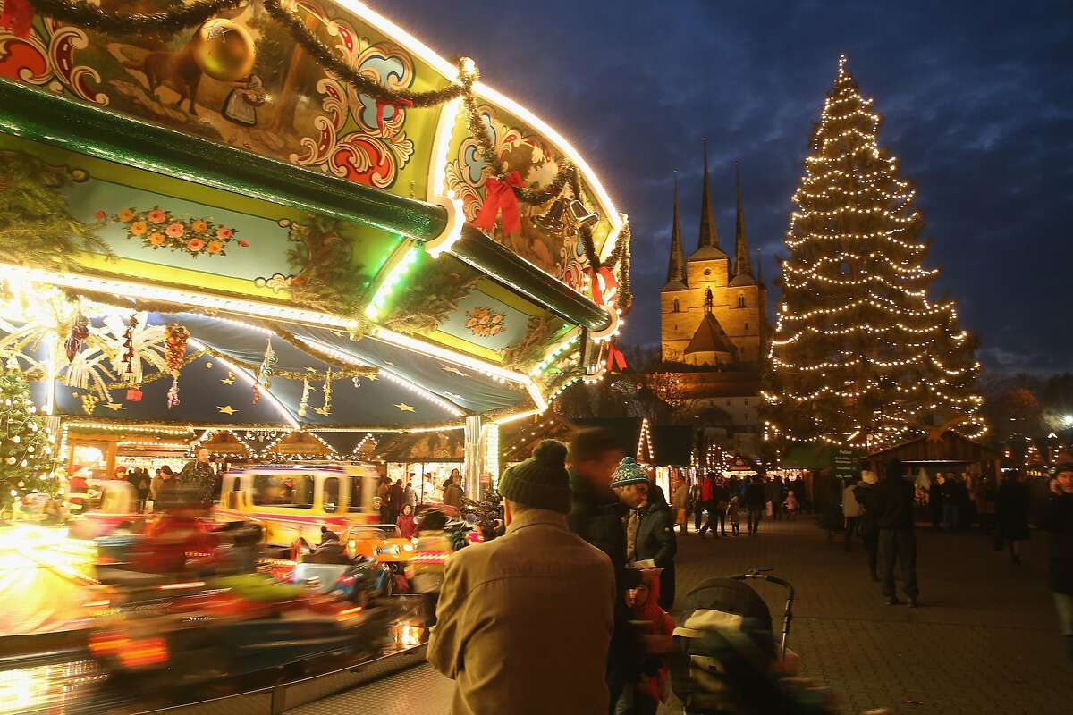 Visitors watch children ride a merry-go-round at the annual Christmas market on Domplatz square in Erfurt, Germany. Christmas markets across Germany opened last week and will stay open through the end of December to sell Gluehwein, Christmas decorations, sweets and other delights.