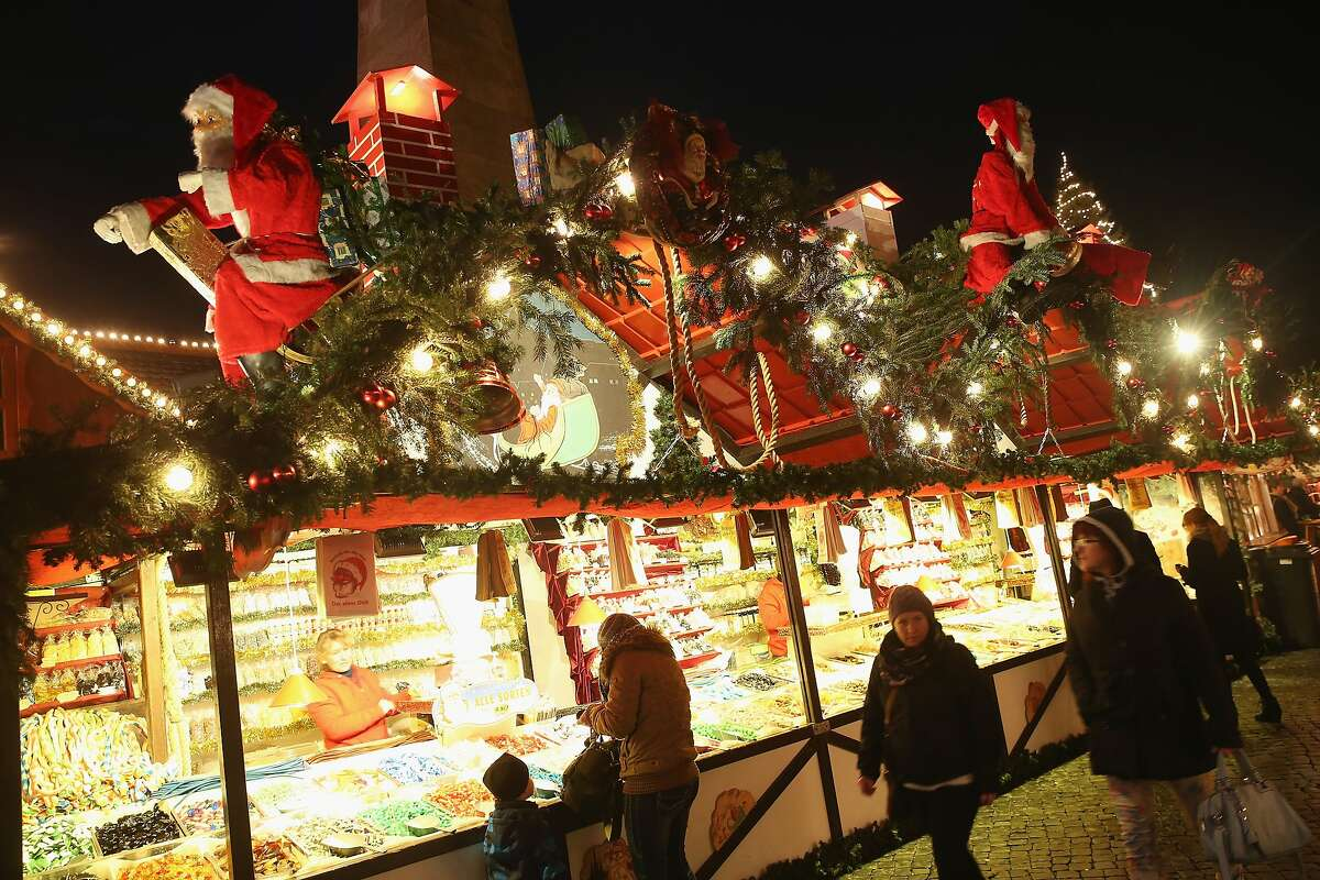 Visitors walk past a stall selling candied nuts and decorated with Santas at the annual Christmas market on Domplatz square on November 26, 2014 in Erfurt, Germany.