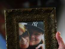 Kimberly Lepenga shows a picture of her with her son, Scott Lovito, inside her home in New Milford, Conn. Tuesday, Feb. 18, 2014.  Lepenga's son died summer 2013 at age 21 of a heroin overdose in which the drug was tainted with the synthetic opiate fentanyl.