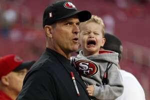 San Francisco 49ers' head coach Jim Harbaugh holds his crying son, Jack, before the Niners play the Seattle Seahawks in NFL game at Levi's Stadium in Santa Clara, Calif., on Thursday, November 27, 2014.
