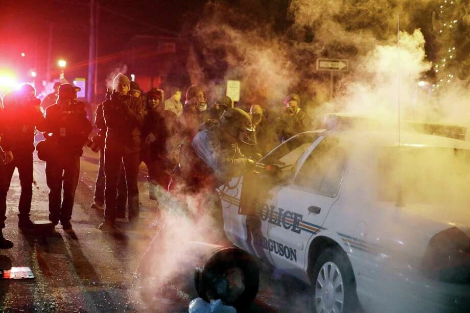 A police officer approach a police vehicle after a protester has thrown a smoke device from the crowd Tuesday, Nov. 25, 2014, in Ferguson, Mo. Missouri's governor ordered hundreds more state militia into Ferguson on Tuesday, after a night of protests and rioting over a grand jury's decision not to indict police officer Darren Wilson in the fatal shooting of Michael Brown, a case that has inflamed racial tensions in the U.S. (AP Photo/David Goldman) Photo: David Goldman, Associated Press / AP