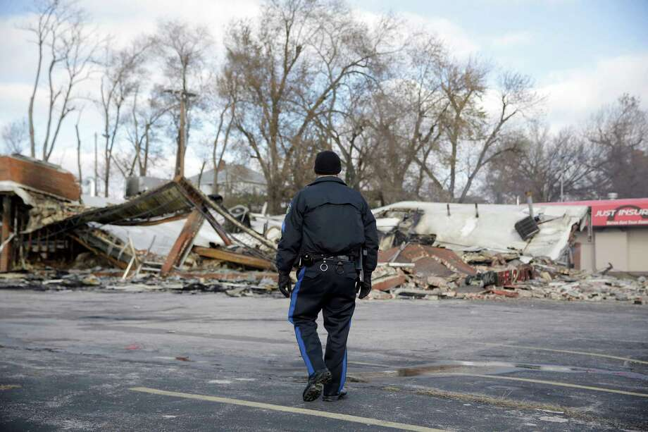 A member of the Missouri Highway Patrol walks past a building burned to the ground, Tuesday, Nov. 25, 2014, in Dellwood, Mo. The building and several others in-and-around Ferguson were burned during protests after a grand jury decided not to indict a Ferguson police officer in the shooting death of Michael Brown. Photo: Jeff Roberson, AP / AP