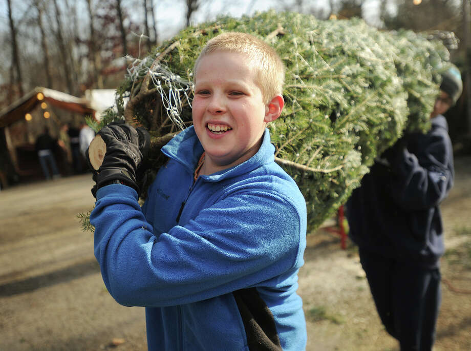 Troop 105 Boy Scouts John Peabody, 13, left, and Johnathan Moger, 13, both of Ansonia, carry a Christmas tree to a customer's car at the troop's annual tree sale fundraiser at Hilltop Hose on Pulaski Highway in Ansonia on Sunday, November 30, 2014. Photo: Brian A. Pounds / Connecticut Post