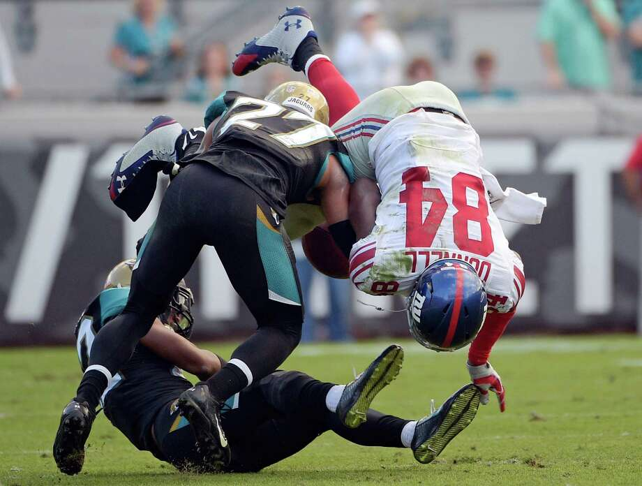 New York Giants tight end Larry Donnell (84) fumbles the ball as he is hit by Jacksonville Jaguars cornerback Dwayne Gratz (27) during the second half of an NFL football game in Jacksonville, Fla., Sunday, Nov. 30, 2014. Jacksonville recovered the fumble and Aaron Colvin returned it for a 41-yard touchdown. (AP Photo/Phelan M. Ebenhack) ORG XMIT: JVS118 Photo: Phelan M. Ebenhack / FR121174 AP
