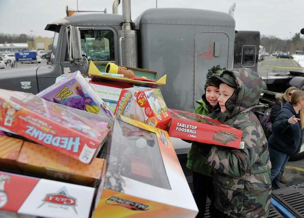 Brady Scianna, left, 6, from Burnt Hills and Evan Farrar, 6, from Ballston Spa place toys they brought into a box at the Convoy for Tots 2014 on Sunday, Nov. 30, 2014, in Wilton, N.Y.  Farrar at his birthday party in November, had friends bring gifts for Toys for Tots instead of for him.  Scianna at his birthday party in October had friends bring toys for dogs which were given to the Saratoga Animal Shelter.  The convoy event was put on by the Capital Region Toys for Tots and the Saratoga County Sheriff's Office to collect more toys for the Toys for Tots program.  The convoy was made up of emergency services agencies from Saratoga County and members of the public who had a truck of any size and wanted to take part.  The convoy traveled through Saratoga Springs and ended up at the Saratoga County Sheriff's Office in Ballston Spa.  All those taking part in the convoy were asked to bring new, unwrapped toys.   (Paul Buckowski / Times Union) Photo: Paul Buckowski / 00029670A