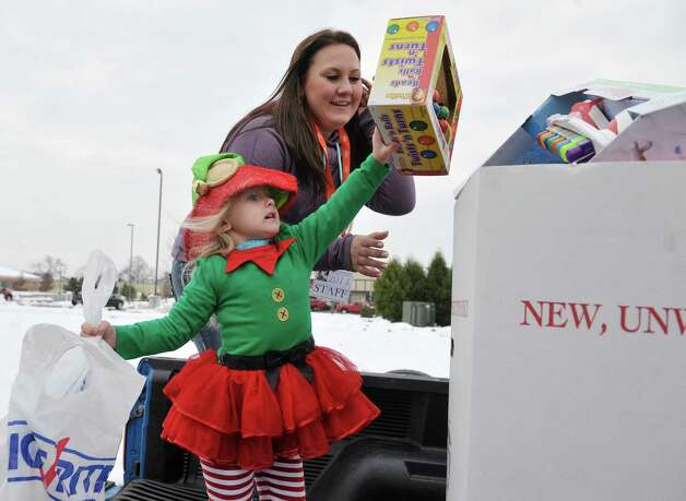 Payton Gill, 4, from Corinth places a gift she brought into a box as Toys for Tots volunteer, Brooke Prevost of South Glens Falls helps at the Convoy for Tots 2014 on Sunday, Nov. 30, 2014, in Wilton, N.Y.   The event was put on by the Capital Region Toys for Tots and the Saratoga County Sheriff's Office to collect more toys for the Toys for Tots program.  The convoy was made up of emergency services agencies from Saratoga County and members of the public who had a truck of any size and wanted to take part.  The convoy traveled through Saratoga Springs and ended up at the Saratoga County Sheriff's Office in Ballston Spa.  All those taking part in the convoy were asked to bring new, unwrapped toys.   (Paul Buckowski / Times Union) Photo: Paul Buckowski / 00029670A