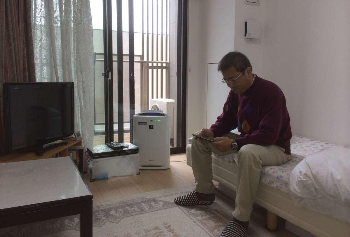 Ryogi Iwasawa monitors his daily energy usage via a tablet app in his apartment at Kashiwa-no-ha.