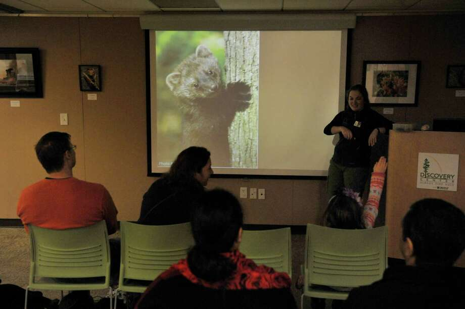 Sara Poggi, background right, an environmental educator at the Albany Pine Bush talks about fishers  during the Feisty Fishers program at the Albany Pine Bush on Sunday, Nov. 30, 2014, in Albany, N.Y.  Participants were educated on facts about the fisher before they headed out onto the trails to look for signs of the fisher and other animals that live in the pine bush.  The Pine Bush will have an all ages Almost Full Moon Hike program on Friday evening Dec. 5th and a all ages Paper Making program on Saturday Dec. 6th.  (Paul Buckowski / Times Union) Photo: Paul Buckowski