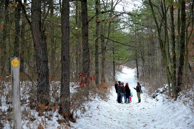Sara Poggi, right, an environmental educator at the Albany Pine Bush leads a group down a trail during the Feisty Fishers program at the Albany Pine Bush on Sunday, Nov. 30, 2014, in Albany, N.Y.  Participants were educated on facts about the fisher before they headed out onto the trails to look for signs of the fisher and other animals that live in the pine bush.  The Pine Bush will have an all ages Almost Full Moon Hike program on Friday evening Dec. 5th and a all ages Paper Making program on Saturday Dec. 6th.  (Paul Buckowski / Times Union) Photo: Paul Buckowski
