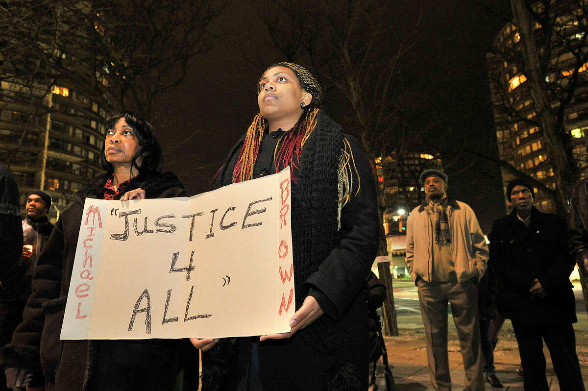 """Norwalk residents Beverly McFadden, left, and her daughter Robbyn McFadden hold a sign during the NAACP rally at the Stamford Government Center in Stamford, Conn., on Sunday, Nov. 30, 2014. The rally was in response to the St. Louis grand jury failing to indict Ferguson Police Officer Darren Wilson in the shooting death of Michael Brown Jr. Beverly said, """"At the end of the Pledge of Allegience (it states) in justice for all, where was the justice for Michael Brown? It did not exist."""""""